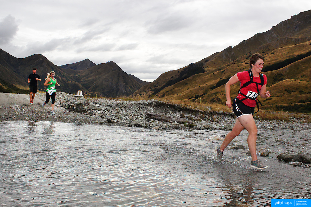 Runner Sally Sally crosses Moke Creek on the Ben Lomond High Country Station during the Pure South Shotover Moonlight Mountain Marathon and trail runs. Moke Lake, Queenstown, New Zealand. 4th February 2012. Photo Tim Clayton