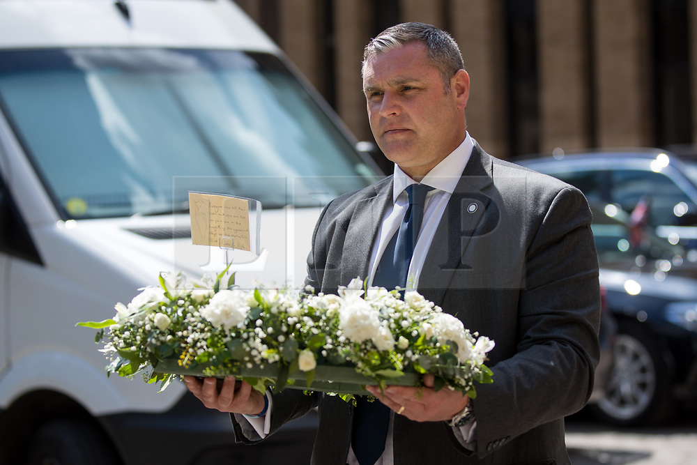 © Licensed to London News Pictures. 03/06/2018. London, UK. A man arrives with flowers displaying a note from the Metropolitan Police Commissioner Cressida Dick, marking one year since the London Bridge and Borough Market terror attacks. A series of events have taken place throughout the day, including a service of commemoration at Southwark Cathedral, the planting of an olive tree in the Cathedral grounds, a minute's silence at 4:30pm and the laying of flowers.  Photo credit : Tom Nicholson/LNP