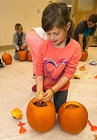 Jazmyn Davidson rolls up her sleeves and digs out the guts of her pumpkin during pumpkin carving at the Boys and Girls Club for Saturday's Pumpkin Fest.  (Karen Bobotas/for the Laconia Daily Sun)
