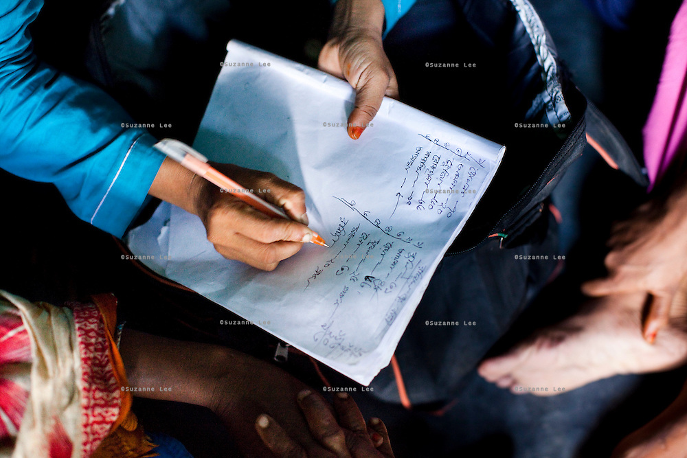 Jesmin Akhter, 26 (in turquoise & blue), keeps a record of her list of credit sales as she sells her products in one of her 'marketplaces', Jerai Villlage, Gobindagonj Upazila, Gaibandha, Bangladesh on 19th September 2011. She has found financial independence and contributes to her household income by working as a saleswoman, earning 3500 - 5000 Bangladeshi Taka per month. She is the top saleswoman under her 'hub', out of 30 women. Having worked for about 2.5 years, she cycles from village to village and door to door in a country where women on bicycles is an extremely uncommon sight. She is one of many rural Bangladeshi women trained by NGO CARE Bangladesh as part of their project on empowering women in this traditionally patriarchal society. Named 'Aparajitas', which means 'women who never accept defeat', these women are trained to sell products in their villages and others around them from door-to-door, bringing global products from brands such as BATA, Unilever and GDFL to the most remote of villages, and bringing social and financial empowerment to themselves.  Photo by Suzanne Lee for The Guardian