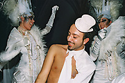 A man with a small top hat dances with two woman with large headdresses at Return to Narnia, Pushca, New Years Eve, 2004