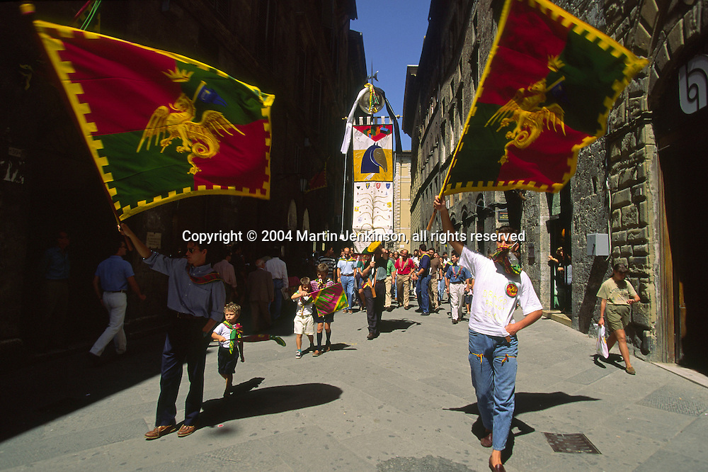 Members of the Contrada Drago winners of the Palio (banner) parade it through the streets of Siena....travel, lifestyle