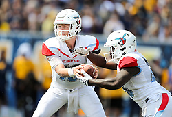 Sep 16, 2017; Morgantown, WV, USA; Delaware State Hornets quarterback Jack McDaniels (10) hands the ball off to Delaware State Hornets running back Mike Waters (25) during the first quarter against the West Virginia Mountaineers at Milan Puskar Stadium. Mandatory Credit: Ben Queen-USA TODAY Sports