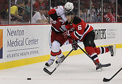 Oct 10; Newark, NJ, USA; New Jersey Devils defenseman Andy Greene (6) and Carolina Hurricanes center Tuomo Ruutu (15) battle for the loose puck during the first period at the Prudential Center.