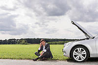 Full length of unhappy young businessman using cell phone by broken down car at countryside