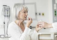 Seniorin nimmt Medikament ein (model-released)