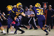 Milpitas High School quarterback Ronnie Reed (7) hands the ball off to Sean Barnes (30) against Fremont at Milpitas High School in Milpitas, California, on November 1, 2013. (Stan Olszewski/SOSKIphoto)