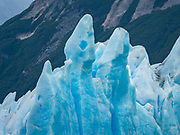 Tall seracs of Perito Moreno Glacier, El Calafate, Santa Cruz Province, Argentina, Patagonia, South America. The spectacular Perito Moreno Glacier is one of 48 glaciers fed by the Southern Patagonian Ice Field (the world's third largest reserve of fresh water). Moreno Glacier melts into Lake Argentino, surrounded by Los Glaciares National Park. Lago Argentino is the biggest freshwater lake in Argentina and reaches as deep as 500 meters (1640 feet). Its outlet, the Santa Cruz River, flows into the Atlantic Ocean. Despite most glaciers worldwide retreating due to global warming, Perito Moreno Glacier has been a relatively stable exception for the past hundred years. Located 78 kilometers (48 mi) from El Calafate, the glacier was named after explorer Francisco Moreno, a pioneer who studied the region in the 1800s and defended the territory of Argentina in the conflict surrounding the international border dispute with Chile. Los Glaciares National Park is honored on UNESCO's World Heritage List.