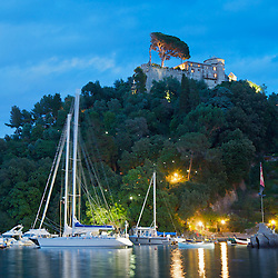 Castello Brown stands perched above small sailboats moored in Portofino, Italy at night.