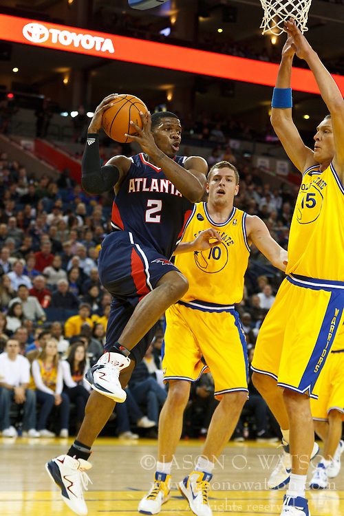 February 25, 2011; Oakland, CA, USA;  Atlanta Hawks shooting guard Joe Johnson (2) shoots past Golden State Warriors center David Lee (10) and center Andris Biedrins (15)  during the first quarter at Oracle Arena. Atlanta defeated Golden State 95-79.