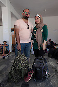 Tarik Aljadoue (34) and his wife Samar Jamal (27) at the space that NGO Aggalia has organised as a temporary stop for refugees in Kaloni village, as they are on their way to Mytilene city. A local person drove them there the night before. The couple is from Alepo in Syria where Tarik was working as an IT engineer for a French owned oil company until they closed down their business there in 2011. Since 2011 he moved to Kafarhamra north of Alepo, as his house in Alepo was in a dangerous area. He got married to Samar one year ago and they were waiting to see what will happen to their country. 6 months ago internet was cut so it was difficult to learn any news of what was really happening. Local TV was only broadcasting propaganda from different armies. On Friday one week ago, they decided to find a safe country to have their children and leave Syria where they saw no work and no future as they could not see the end of this war. They want to try to reach Germany or any other European country where they can find work. <br /> Their trip started from Alepo to Tartus by bus, then on an other bus to a port from where they boarded a ship for one and a half day to Toshojo port (Tasucu port?) in Turkey near Mersin. From there they took a bus for 13 hours to Izmir but before they arrive they heard that there were police checks in Izmir and as soon as they arrived, they boarded an other bus for 9 hour to Istanbul. There they stayed for two days until the smugglers told them that they could start their trip to Greece. They payed 1250 USD each and after two days, at 8 am, they met the smugglers at a metro station, they boarded a bus with 60 people and no AC and they traveled to a location near Izmir. The trip lasted for 7 hours and it was unbearably hot. When they got off the bus somewhere near the sea, they were told to switch off their mobile phones and walk for one hour until they reached the sea. There there were three dinghy boats with engines and 33 to 40 people would board on each