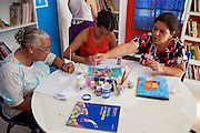 Some of the childrens mothers painting one of the characters from a book on to a tea towel in the community library, Biblioteca Comunitaria do Arquipelago, Porte Alegre, Brazil. <br /> <br /> Cirandar is working in partnership with  C&A and C&A Instituto to implement a network of Community Libraries in eight communities of Porto Alegre.