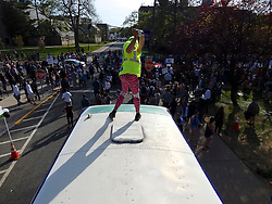 New York artist Mary Mihelic and Philadelphia artist DAVID GLEESEN, seen here playing golf from the bus' roof top, drove a former Trump-Campaign bus turned art installation to the April 25, 2016 Trump rally. Trump-Supporters and anti-Trump protestors face each other outside a rally of the Republican candidate, held at the campus of West Chester University in West Chester, Pennsylvania a day ahead of the Pennsylvania Primary.