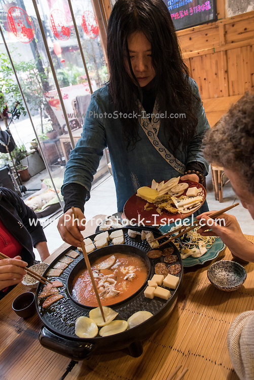 Hot Pot Restaurant in Chengdu, Sichuan, China. The food is cooked in a broth at the table
