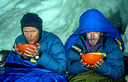 Climbers eat dinner  - 3 day bivouac in shelter of crevasse on 7300m peak 1st ascent Chongtar, Karakoram Mts, far western China, Central Asia