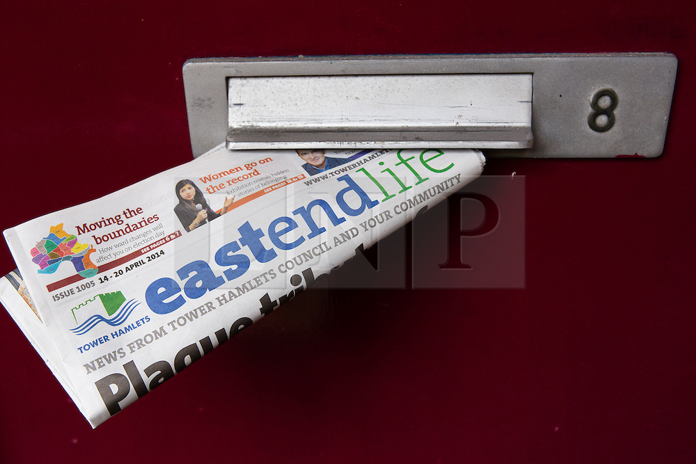 © Licensed to London News Pictures. 19/04/2014. London, UK. A  copy of Tower Hamlets council newspaper, East End Life in a residential letterbox in East London. East End Life is delivered free to over 83,000 homes and businesses in Tower Hamlets each week. Communities minister, Eric Pickles has demanded that five Labour-run London councils, including Tower Hamlets stop publishing free council funded newspapers and has given them a two-week ultimatum to explain why they should not face legal action for breaching publicity code. Photo credit : Vickie Flores/LNP.