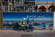 A workman pushes a dustcart walks past a billboard showing the future skyline of London, including the new 1, Blackfriars which will be a 52-storey tower (170m).