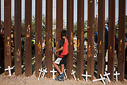 A boy looks through the U.S.-Mexico border wall in Nogales, Sonora with crosses left for migrants who died at his feet on November 11, 2017 during an immigration-focused rally held by the SOA Watch on both sides of the border.