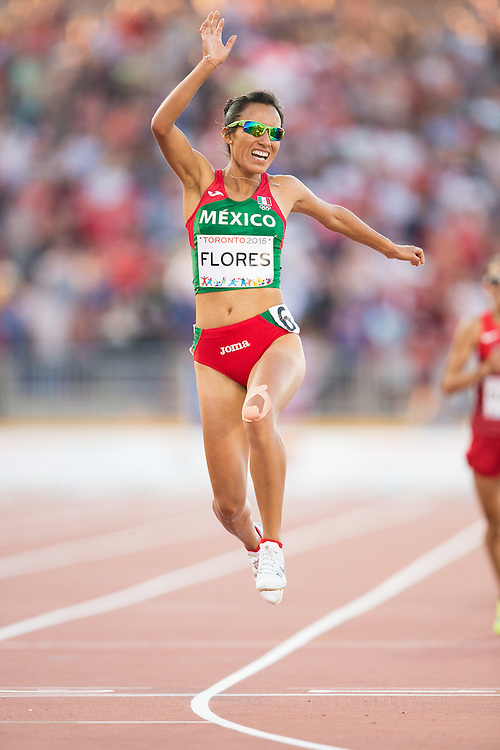 Brenda Flores of Mexico celebrates her gold medal win in the women's 10000 metres at the CIBC Athletics Stadium at the at the 2015 Pan American Games in Toronto, Canada, July 23,  2015.  AFP PHOTO/GEOFF ROBINS