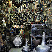 A shop selling Jambiyas, the traditional Yemeni sword worn around the waist by men, jewlery, and other traditional Yemeni wares, in the central souq of Old San'aa. UNESCO, the United Nations cultural organization, declared San'a a world heritage site in 1988. San'a was a trade capital as early as the 1st century B.C. With merchants crowded  inside the mud walls of the city, the San'anis built upwards -- as high as nine stories, an impressive feat given the technology of the time. San'aa's homes rest on lower stories built of stone; some date to the 9th or 10th centuries. Over generations, families added floors in brick, making each new floor slightly smaller than the previous one for stability.