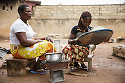 Josephine Akissi Coulibaly, 52, a former FGM/C practitioner, sits with her eldest daughter, Christine Coulibaly Ndaglihi, 18, at their home in the town of Katiola, Cote d'Ivoire on Friday July 12, 2013. Josephine abandoned the practice thanks to advocacy work by UNICEF partner organization OIS Afrique.<br /> <br /> <br /> Mme Coulibaly Akissi Josephine, 52, exciseuse<br /> Coulibaly Ndaglihi Christine, 18, oldest daughter, not excised.