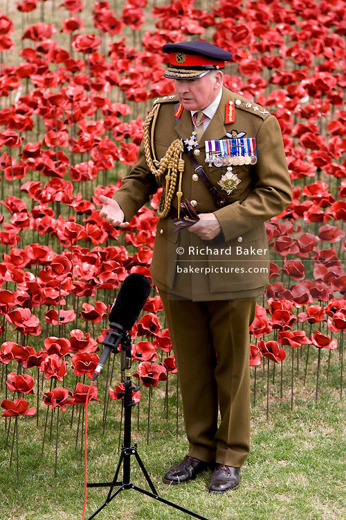 Marking the centenary of the beginning of the First World War (WW1) in 1914, General the Lord Dannatt is interviewed for TV among some of the ceramic poppies created by artist Paul Cummins. Remaining in place until the date of the armistice on November 11th. Across the world, remembrance ceremonies for this historic conflict that affected world nations. General Francis Richard Dannatt, Baron Dannatt, GCB, CBE, MC, DL (born 1950) is a retired British Army officer and the incumbent Constable of the Tower of London.