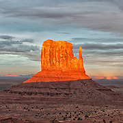 Monument Valley's West Mitten illuminates at sunset.