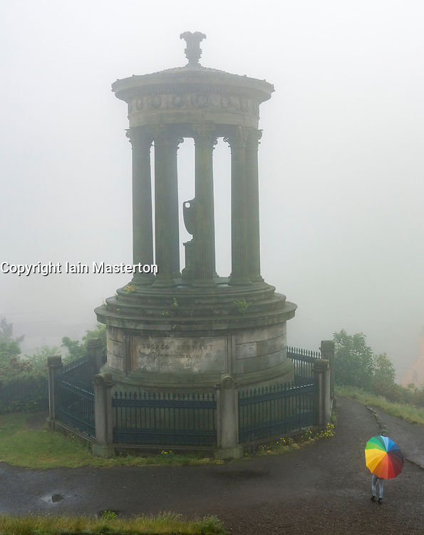 Woman with colourful umbrella and Dugald Stewart monument Calton Hill on foggy , rainy day, Edinburgh, Scotland, UK