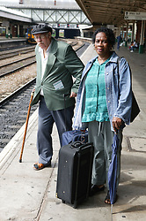 Man and woman waiting on railway platform for a train,