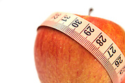 Diet concep Cutout of a tape measure wrapped around an apple on white background