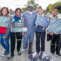 Cody High School Asst Football Coach and school counselor Jimmie Knight poses with students before game.