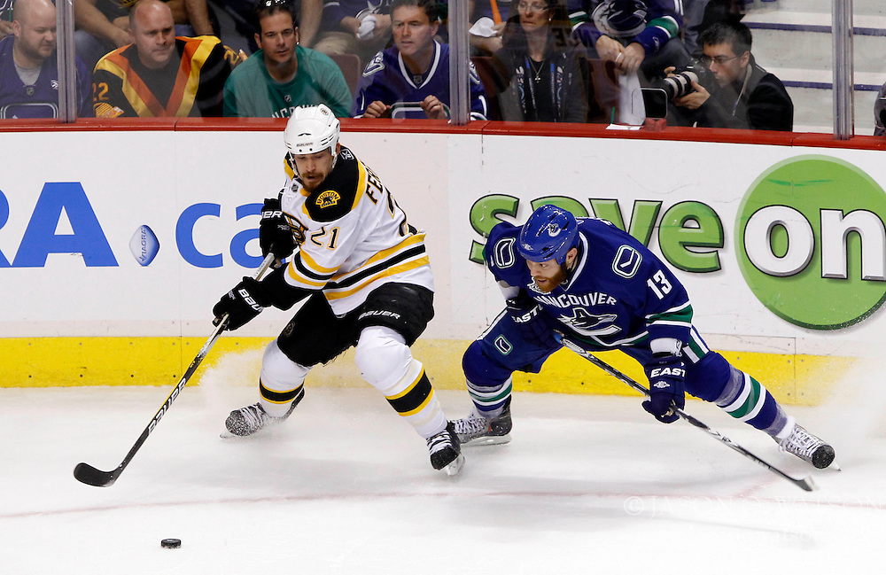 June 15, 2011; Vancouver, BC, CANADA; Boston Bruins defenseman Andrew Ference (21) takes the puck away from Vancouver Canucks left wing Raffi Torres (13) in the first period of game seven of the 2011 Stanley Cup Finals at Rogers Arena. Mandatory Credit: Jason O. Watson / US PRESSWIRE