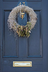 December 21, 2017 - Charleston, South Carolina, United States of America - A low country style Christmas wreath made from Spanish Moss hangs from a wooden door on a historic home along the Battery in Charleston, SC. (Credit Image: © Richard Ellis via ZUMA Wire)