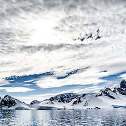 A layer of high clouds partially obscures the sun above Cuverville Island on the western side of the Antarctic Peninsula.