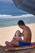 A little girl in her daddy's lap laughs happily at her father on the beach