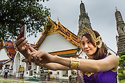 "23 SEPTEMBER 2013 - BANGKOK, THAILAND: A tourist dressed in a costume of the Royal Thai court circa 1800 takes pictures of herself with her iPhone in front of the central prang at Wat Arun. The outstanding feature of Wat Arun is its central prang (Khmer-style tower). The world-famous stupa will be closed for three years to undergo repairs and renovation along with other structures in the temple compound. This will be the biggest repair and renovation work on the stupa in the last 14 years. In the past, even while large-scale work was being done, the stupa used to remain open to tourists. It may be named ""Temple of the Dawn"" because the first light of morning reflects off the surface of the temple with a pearly iridescence. The height is reported by different sources as between 66,80 meters and 86 meters. The corners are marked by 4 smaller satellite prangs. The temple was built in the days of Thailand's ancient capital of Ayutthaya and originally known as Wat Makok (The Olive Temple). King Rama IV gave the temple the present name Wat Arunratchawararam. Wat Arun officially ordained its first westerner, an American, in 2005. The central prang symbolizes Mount Meru of the Indian cosmology. The temple's distinctive silhouette is the logo of the Tourism Authority of Thailand.           PHOTO BY JACK KURTZ"
