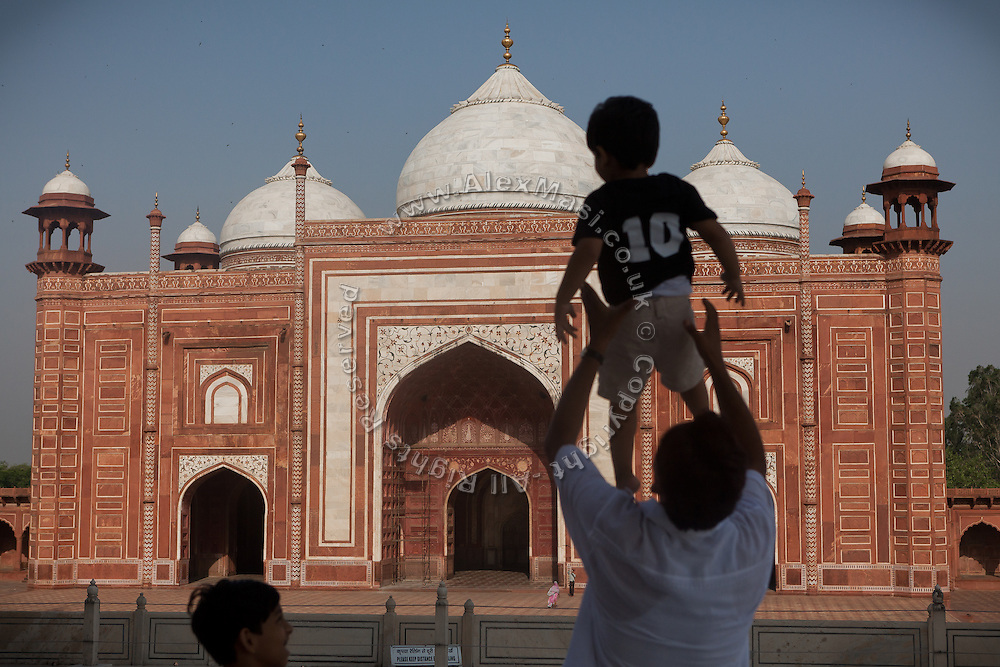 Visitors are enjoying a day at the Taj Mahal complex overlooking the mosque, in Agra.