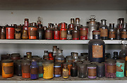 Shelf of bottles of coloured pigments used to mix dyes, in the Atelier de Teinture or Dyeing Workshops, at the Gobelins Manufactory, a historic tapestry workshop, at Le Mobilier National, which commissions and conserves state furniture, in the 13th arrondissement of Paris, France. The dyeing workshop was founded by Colbert in 1665, when a limited palette of natural dyes were used. In 1838 Eugene Chevreul created his chromatic circle, which is now digitised and used for mixing synthetic dyes. Picture by Manuel Cohen