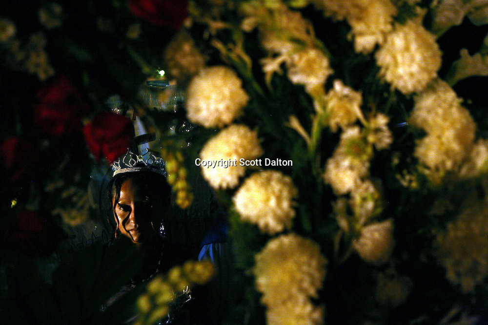 A follower of Nino Fidencio, a curandero or healer who passed away in the 1938, is seen through a wreath of flowers brought in honor of El Nino in Espinazo, Mexico on October 16, 2006. Followers of Nino Fidencio believe that his spirit can posses other healers, who once possessed speak in a child like voice and perform a variety of medical cures on their followers. His believers, an estimated 20,000, gather in his hometown for a three-day festival twice a year in March and October. (Photo/Scott Dalton)