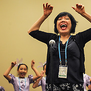 Jing Ling-Tam, a professor of music at the University of Texas at Arlington, demonstrates vocal exercises to the Little Lark Choir and Autumn Whispers Choir, both from China, during a World Choir Games workshop on Friday morning, July 6, 2012, in the Duke Energy Convention Center.  The exercises are designed to help participants maintain their singing voices as they age. Also at the workshop were the Columbus (Ohio) International Children's Choir and Santa Gema Youth Choir from Puerto Rico.