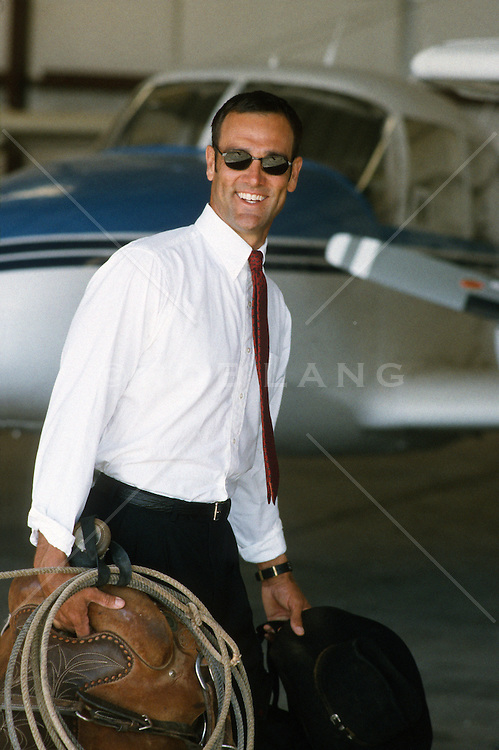 Texas business man carrying his saddle and lasso in an airport hanger