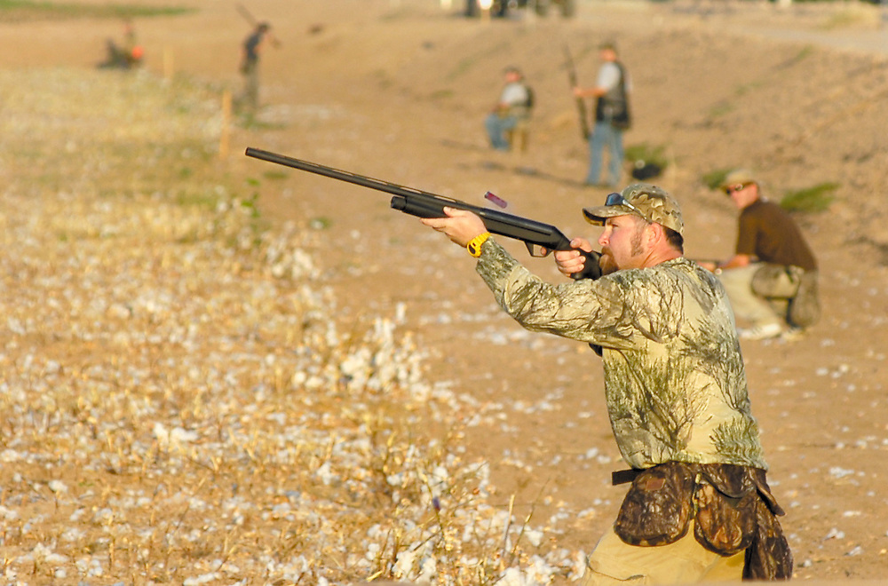 Keith Kershaw of Yuma fires a shot at a low flying morning dove while hunting a cotton field Saturday morning at Curry Farms. Curry Farms is an area where the Southwest Arizona Habitat Partnership Committee set aside several fields as habitat for doves to help ensure a strong dove population in the area. RYAN BRENNECKE/THE SUN