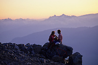 Couple relax on a rock on Blackcomb Mountain, with a purple sunset behind, bike in front