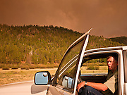 "04 JUNE 2011 - GREER, AZ: Dave Krick (CQ) a year round resident of Greer, takes a last look before evacuating Saturday evening. The fire grew to more than 140,000 acres early Saturday with zero containment. A ""Type I"" incident command team has taken command of the fire.  PHOTO BY JACK KURTZ"