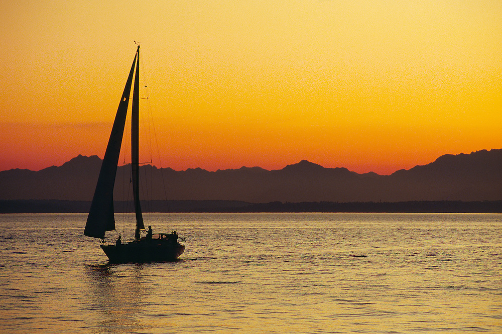 The alpine glow of sunset and the Olympic Mountains provides a majestic backdrop to a lone sailboat as it prepares to dock in Puget Sound outside of Seattle, Washington.  Pacific Northwest.  Summer.  Evening.