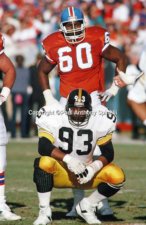 Pittsburgh Steelers defensive end Keith Willis (93) takes a break between plays along with Denver Broncos offensive lineman Gerald Perry (60) during the NFL AFC Divisional playoff football game against the Denver Broncos on Jan. 7, 1990 in Denver. The Broncos won the game 24-23. (©Paul Anthony Spinelli)