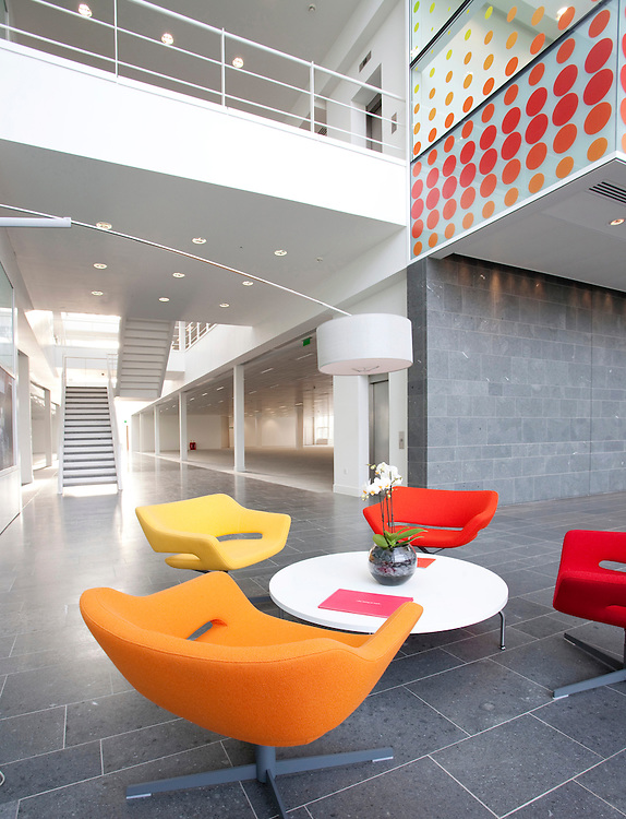 bright coloured chairs in large open plan  office reception