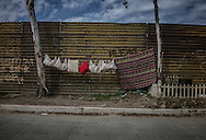 Laundry hung to dry between trees in front of the US-built border fence in Tecate.  Baja California, Mexico.