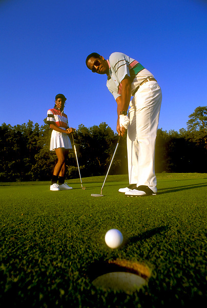 Stock photo of a man about to sink a putt.