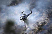 May 15, 2014 - Escondido, California, U.S -<br /> <br /> California Wildfires 2014 - Cocos Fire<br /> <br /> A firefighting helicopter from the San Diego Sheriff's Department drops water on flames in the hills of San Marcos at the Cocos Fire. The 800-acre fire in San Marcos continued to burn out of control Thursday, threatening houses and forcing nearby residents from their homes. The fire burned at least three homes and one structure near Cal State San Marcos.<br /> ©Exclusivepix
